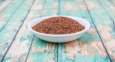 rooibos: Dried South African rooibos herbal tea in white bowl over wooden background Stock Photo