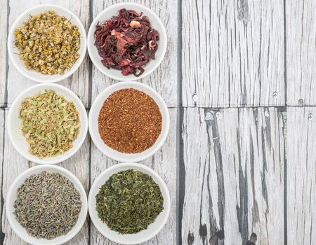 rooibos: Dried herbal tea leaves, lavender, rooibos, chamomile, linden flower, hibiscus, Japanese green tea over wooden background