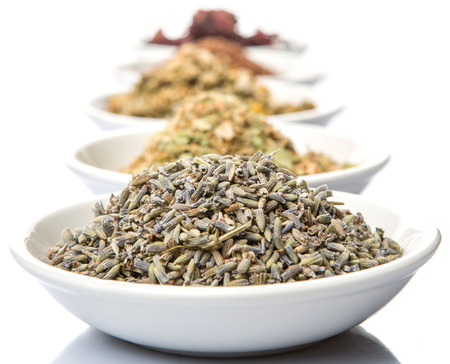 chamomile flower: Dried herbal tea leaves, lavender, rooibos, chamomile, linden flower, hibiscus, Japanese green tea in white bowl over white background