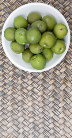 olive green: Pickled green olive in white bowl over wooden background