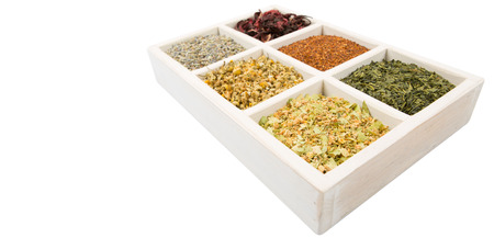 chamomile flower: Dried herbal tea leaves, lavender, rooibos, chamomile, linden flower, hibiscus, Japanese green tea in white wooden box over white background