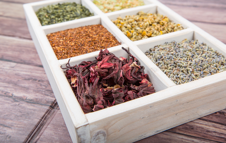 herbs boxes: Dried herbal tea leaves, lavender, rooibos, chamomile, linden flower, hibiscus, Japanese green white box over wooden background