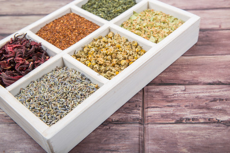 chamomile flower: Dried herbal tea leaves, lavender, rooibos, chamomile, linden flower, hibiscus, Japanese green white box over wooden background