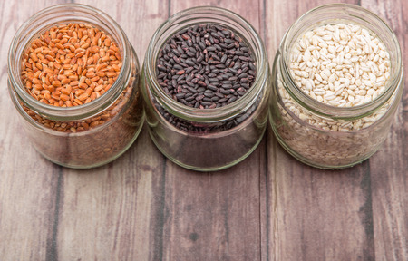free backgrounds: White, brown, black millet in mason jars over wooden background