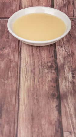 condensed: Sweet condensed milk in white bowl over wooden background