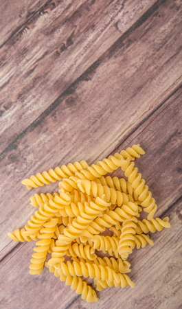 rotini: Dried corkscrew shape pasta or rotini pasta over wooden background