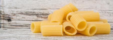 ridged: Rigatoni pasta or tube shaped pasta over wooden background