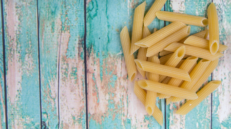 ridged: Dried penne regate pasta over wooden background Stock Photo