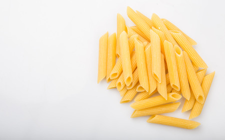 ridged: Dried penne regate pasta over white background Stock Photo