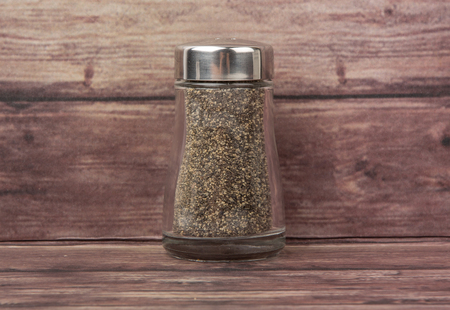 condiment: Peppercorn powder in glass condiment shaker over wooden background Stock Photo