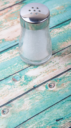 condiment: Table salt in glass condiment shaker over wooden background