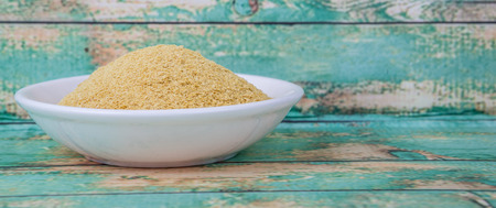 Dried bakers yeast in wooden bowl over wooden background
