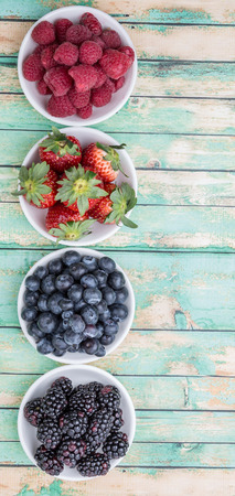 summer fruits: Blackberry, blueberry, strawberry and raspberry in wooden bowl over wooden background