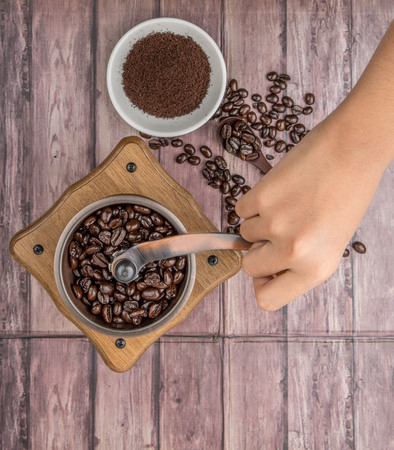grounding: Female hand grounding roasted coffee bean with coffee mill over wooden background