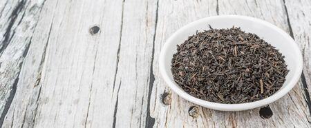 Getrocknete schwarze Teeblätter über Holzuntergrund