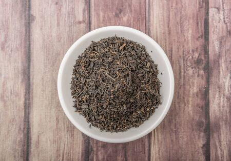 plant antioxidants: Dried black tea leaves over wooden background