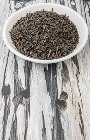 plant antioxidants: Dried black tea leaves in white bowl over wooden background