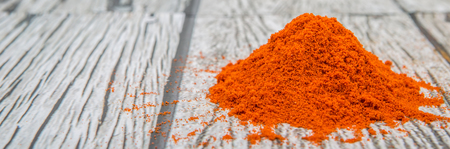 grounded: Cayenne pepper powder over wooden background Stock Photo
