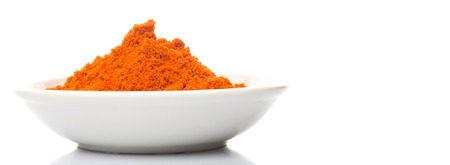 grounded: Cayenne pepper powder in white bowl over white background