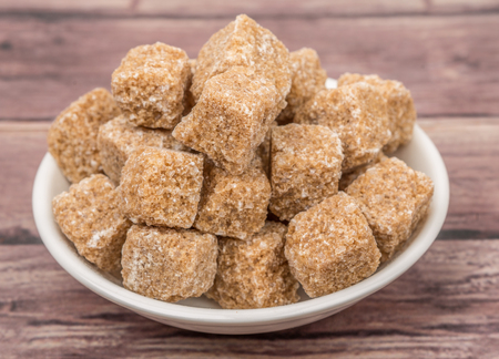 sweetening: Brown sugarcane cubes in white bowl over wooden background Stock Photo