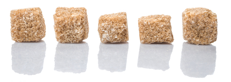 sweetening: Brown sugarcane sugar cube over white background