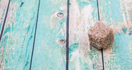 sweetening: Brown sugarcane sugar cube over wooden background