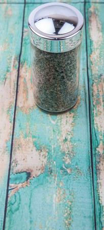 marjoram: Marjoram herbs in spice dispenser over wooden background