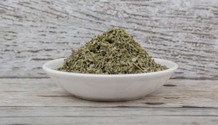 Dried marjoram herbs in white bowl over wooden background