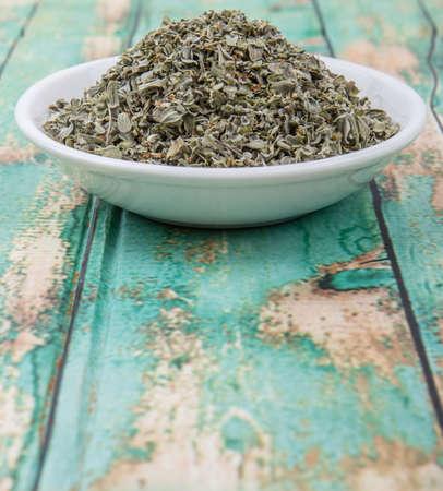 marjoram: Dried marjoram herbs in white bowl over wooden background