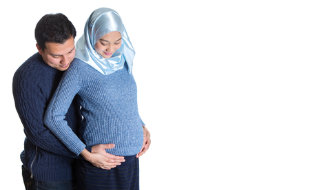 Young happy Muslim pregnant couple over white background
