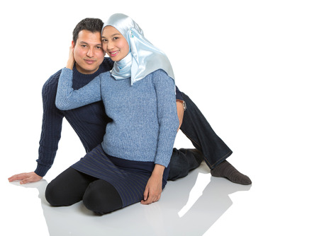 happy asian couple: Young happy Muslim pregnant couple over white background