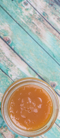 custard flavor: Orange fruit curd in a jar over wooden background