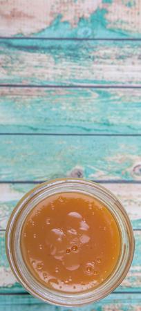 custard flavor: Orange fruit curd in a jar over wooden background