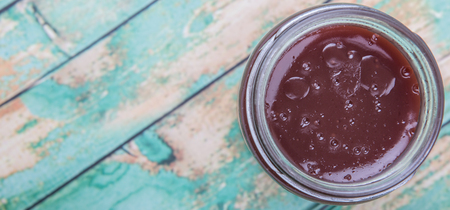 custard flavor: Raspberry fruit curd in glass jar over wooden background