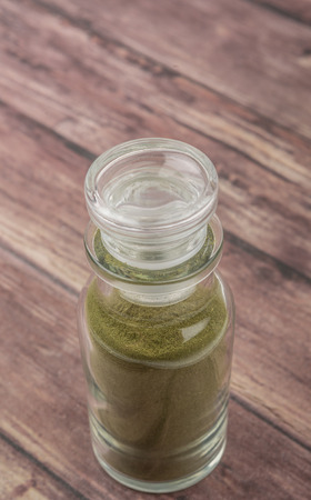 minty: Peppermint herbs powder in glass spice dispenser over wooden background Stock Photo