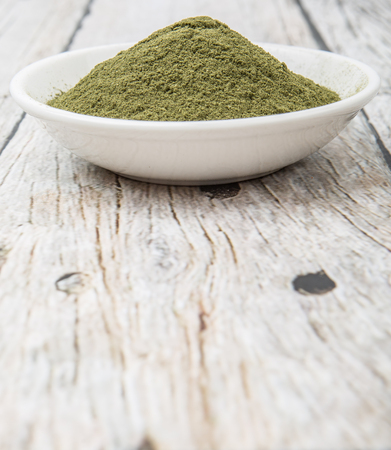 minty: Peppermint herbs powder in white bowl over wooden background