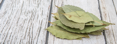 Dried bay leaves herbs over wooden background