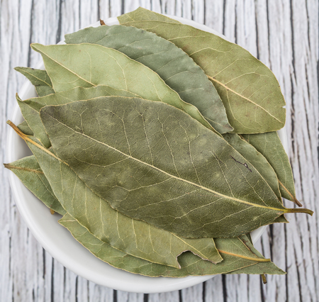 Bay leaves in white bowl over wooden background