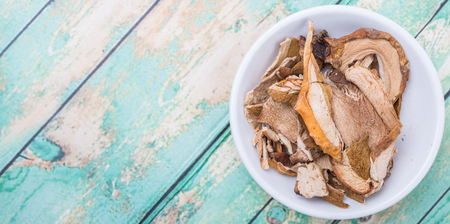 porcini: Dried porcini mushroom in a white bowl over wooden background