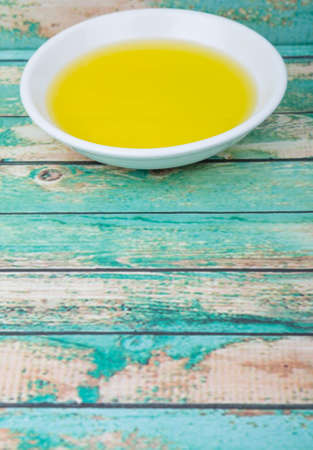 traditional remedy: Olive oil in white bowl over wooden background