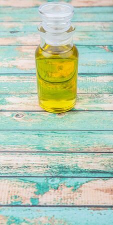 traditional remedy: Olive oil in glass bottle over wooden background