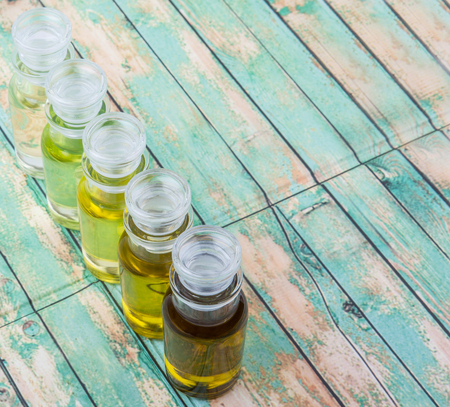 grape seed: Avocado fruit oil, sesame seed oil, olive oil, grape seed oil and corn oil in vial glass bottle over rustic wooden background