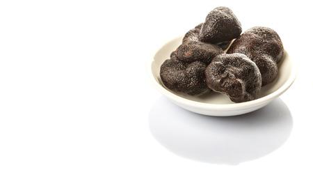 truffe blanche: Truffe noire champignons dans un bol blanc sur fond blanc