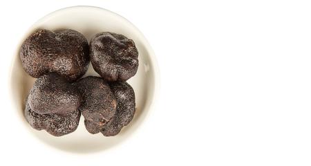 truffe blanche: Black truffle mushroom in white bowl over white background