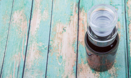 acetic: Maple vinegar in glass vial over wooden background