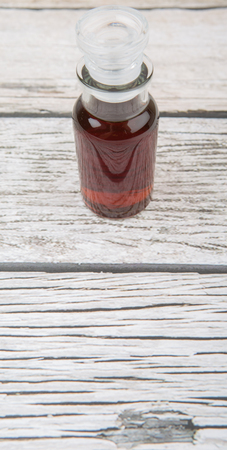 acetic: Maple vinegar in glass vial over wooden background