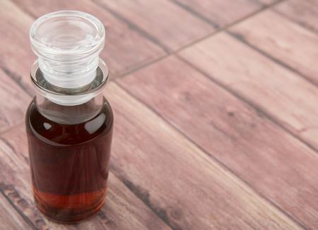 vial: Maple vinegar in glass vial over wooden background