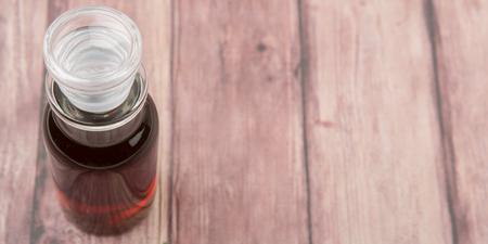 acetic acid: Maple vinegar in glass vial over wooden background