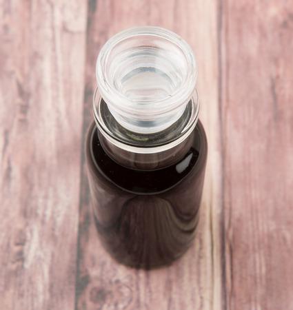 vial: Italian balsamic vinegar in glass vial over wooden background