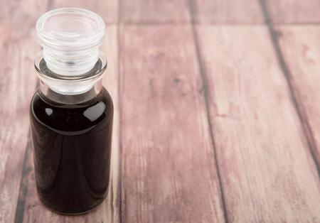 balsamic: Italian balsamic vinegar in glass vial over wooden background